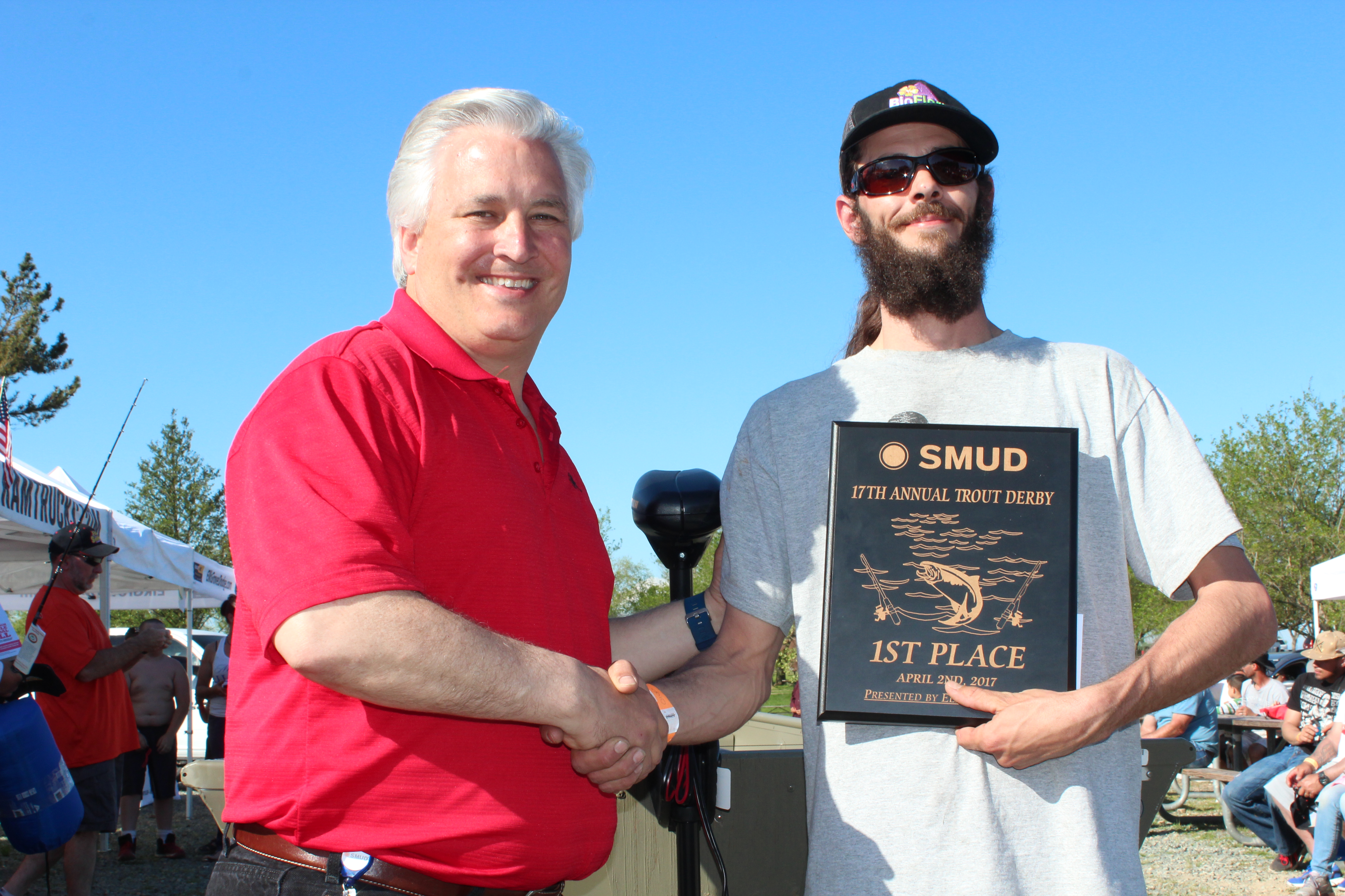 Al Ernst, SMUD's Facilities and Maintenance Supervisor, congratulates Jarred Ross, the first place winner in the adult division on day two of the derby , in front of the14 foot Tracker with a Minn Kota trolling motor that Ross won.